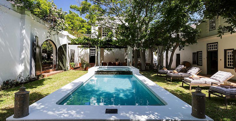 The shade-dappled pool area of the Akademie Street Boutique Hotel.