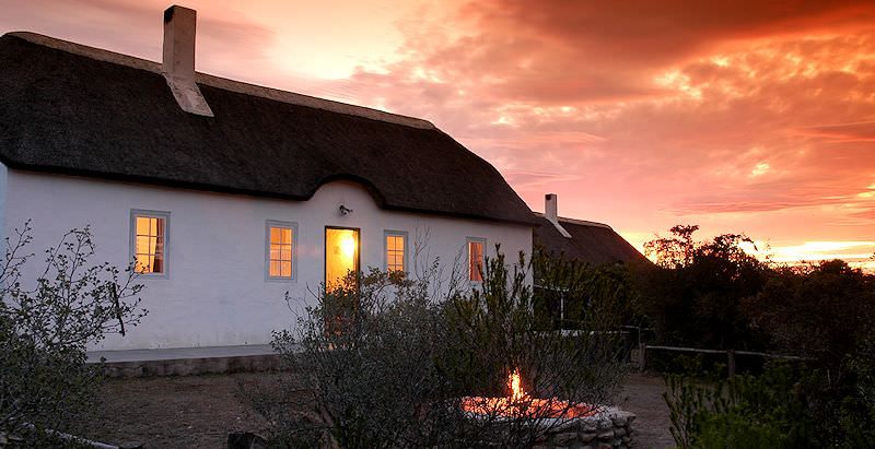 A cozy fire is lit outside a cottage at De Hoop as the sun sets over the reserve.