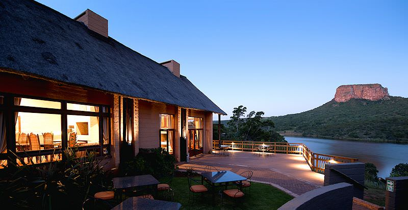 The exterior of Entabeni Lakeside Lodge lit up as evening falls over the Entabeni Conservancy.