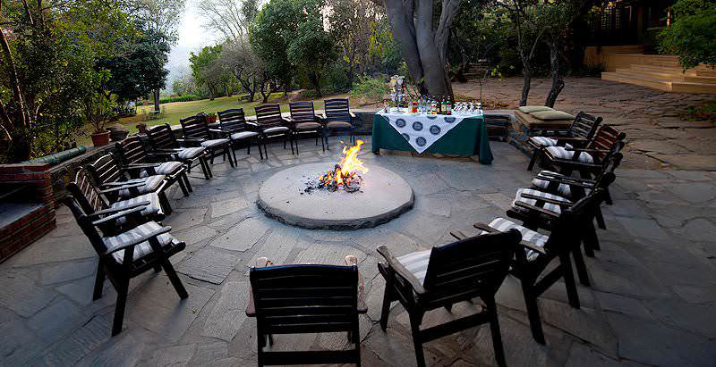 Chairs surround a burning firepit at Fugitives Drift Lodge in the KwaZulu-Natal Battlefields.