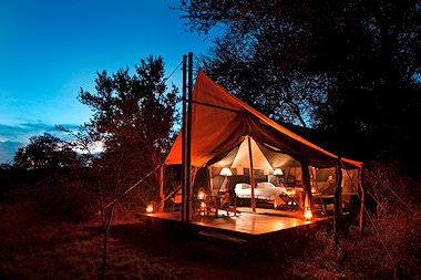 A luxury tent at Plains Camp lit up by lanterns.