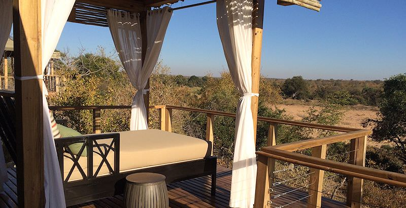 A daybed on the private deck of a tented suite at Simbavati Hilltop Lodge.
