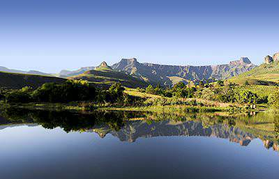 The Drakensberg Mountains reflected in a tranquil pool of water.