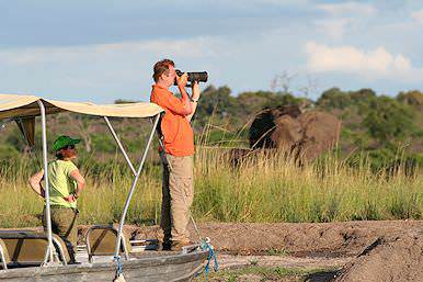 A traveler on safari in the Chobe National Park takes a photograph from a boat.
