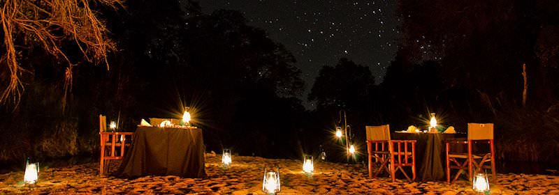 A lantern-lit outdoor dining experience in the bush.