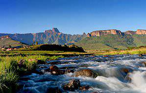 A river bubbles by under the imposing gaze of the Drakensberg mountains.