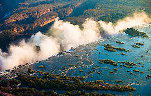 Thick mists billow up above the Victoria Falls.