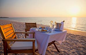 A private dinner for two set up on a remote beach.