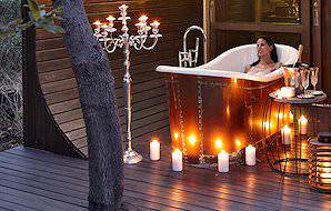 A guest unwinds in a romantic candlelit bath during her honeymoon package.