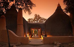 The exterior of Hoyo Hoyo Safari Lodge lit up at night.