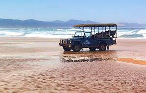 A safari vehicle parked on a beach along the wild shores that fringe Phinda.