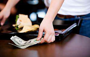 A waitress picks up empty plates and a tip at a table.