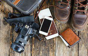 Hiking boots, travel documents, a wallet, a cellphone and a camera.