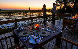 A couple waits for dinner service to begin as the sun sets over the Okavango Delta.