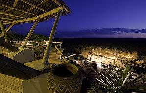 Ongava's sprawling deck offers a view of a waterhole that is lit up at night.