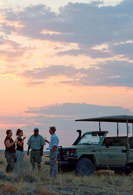 Guests enjoy refreshments during sunset stop on a game drive in Etosha.