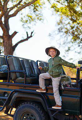 A child mounts a safari vehicle.