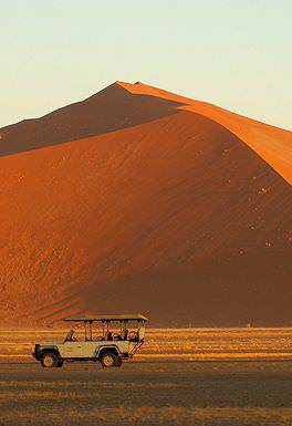 A safari vehicle pauses alongside a dune in Sossusvlei.
