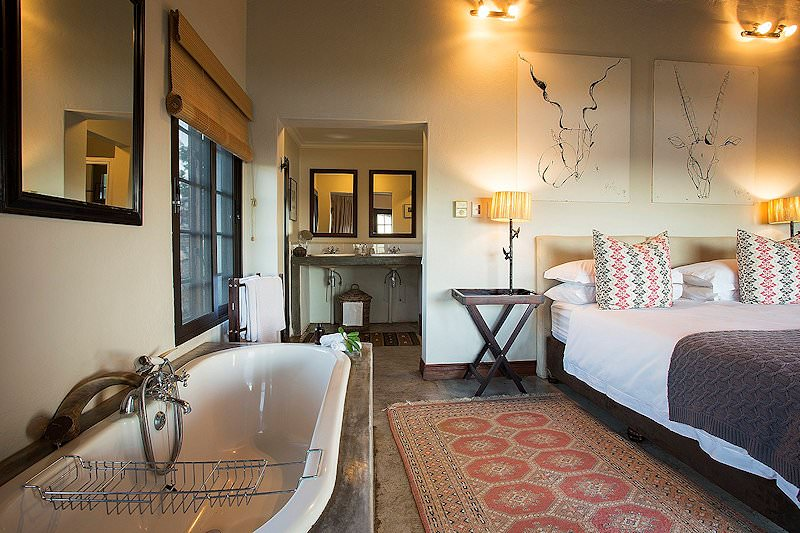 A bathtub and bed in a room at Buhala Lodge.