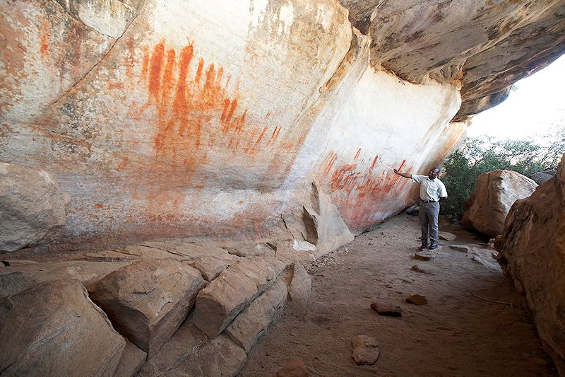 A specialist guide discusses the San rock art behind him.