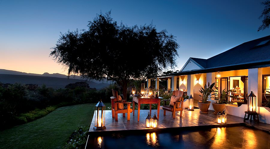 Lanterns light the patio of Koro Lodge as twilight falls over Bushmans Kloof.