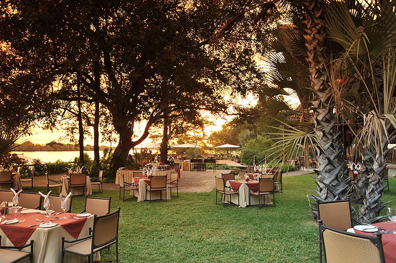 Tables are set up for dinner on the lawns of David Livingstone Safari Lodge.