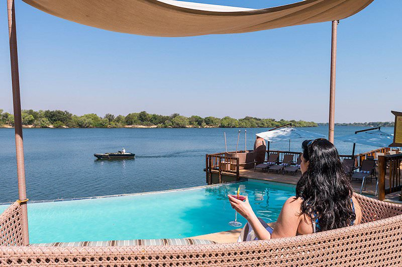 A guest looks out over the Zambezi River from the pool.