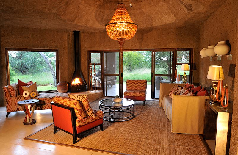 A cozy fire lit in a lounge at Sabi Sabi Earth Lodge.