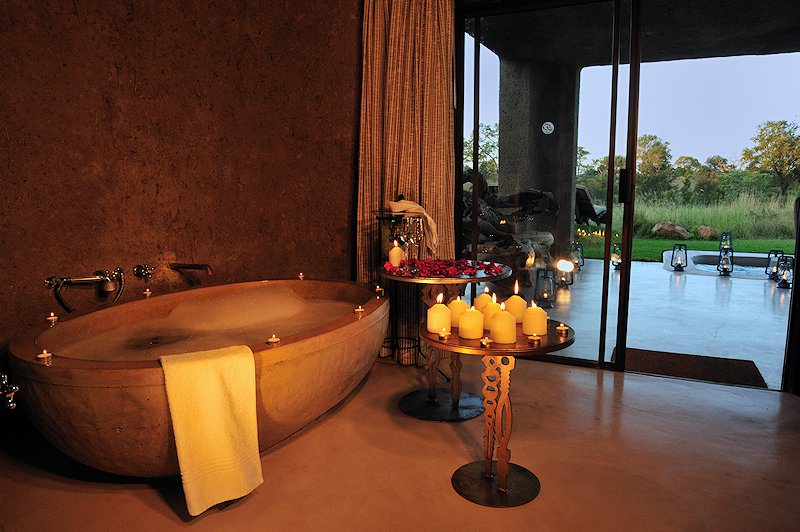 A bathroom at Sabi Sabi Earth Lodge lit up by candles.
