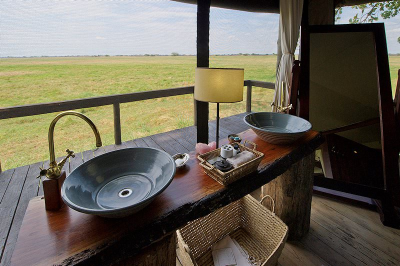 A basin in a bathroom with a view of Kafue National Park.