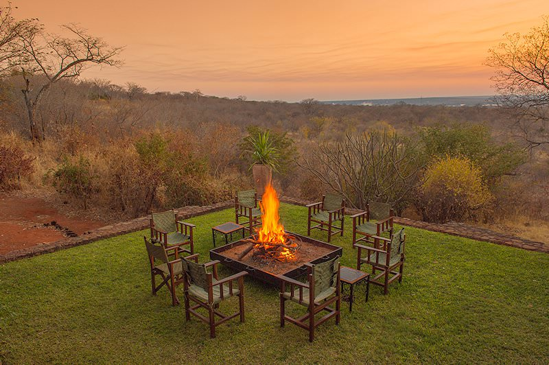 A firepit surrounded by chairs on the lawns of Stanley Safari Lodge.