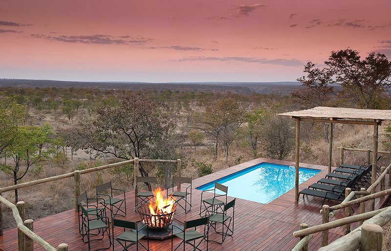 A cozy fire is lit at the pool area at Elephant Camp.