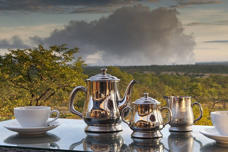 A silver tea set on a table with a view of Victoria Falls National Park.