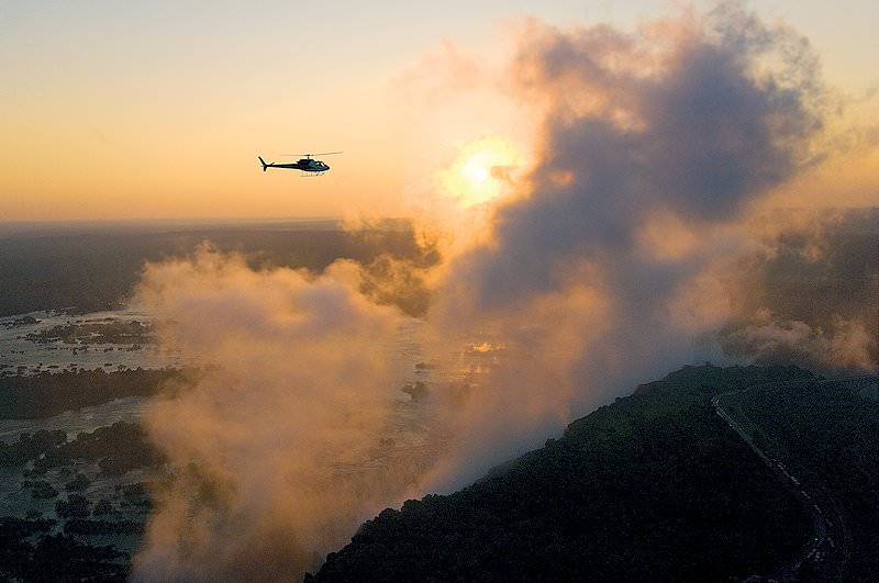 A helicopter flies over the Victoria Falls spraycoud at dusk.