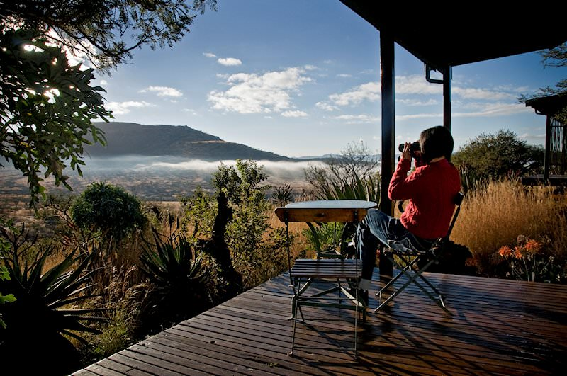 A guest observes wildlife with binoculars at Three Tree Hill Lodge.