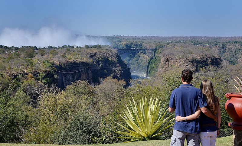 Guests admire the spiraling mists of the Victoria Falls in the distance.