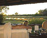 A woman enjoys a hot stone massage with a view of the magnificent Okavango Delta.