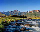 The dramatic Drakensberg Mountains loom above a bubbling brook.
