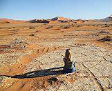 A traveler takes a quiet moment to enjoy the breathtaking scenery of Sossusvlei.