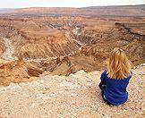 A traveler perched on one of the jagged ridges of Namibia's Fish River Canyon.