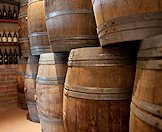 Old wine barrels stacked together in a cellar.