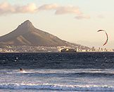 A kitesurfer in Table Bay with Lion's Head in the background.