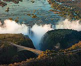 An aerial view of the Victoria Falls bridge with the Falls in the background.