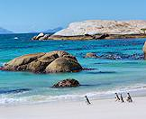 A huddle of penguins waddle along the shores of Boulders Beach.