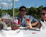 Guests enjoy a bottle of wine and lunch on a river barge.