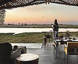 A couple enjoys a tender moment on the deck of their private suite in the Okavango Delta.