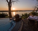 A table set for sunset dinner on the edge of the Zambezi River.