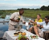 Guests enjoy champagne and snacks on board a powerboat in the Okavango Delta.