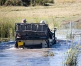 A game drive vehicle drives through a waterway in the Okavango Delta.
