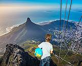 A child looks down at Lion's Head from the top of Table Mountain.
